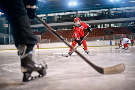 Photo pour Hockey match at rink player in action kicking on goal - image libre de droit