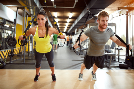 Photo for Young couple on body training in gym - Royalty Free Image