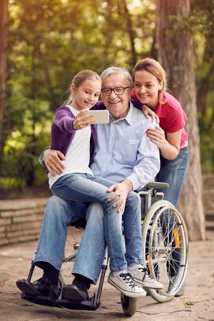 Photo for family selfie time in the park - granddaughter, daughter and disabled man in wheelchair - Royalty Free Image