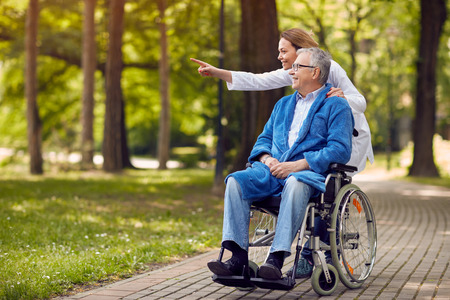 Photo for nurse showing something to elderly man on wheelchair in the park - Royalty Free Image