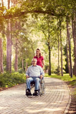 Foto de smiling daughter in the park pushing enjoying senior man in wheelchair - Imagen libre de derechos