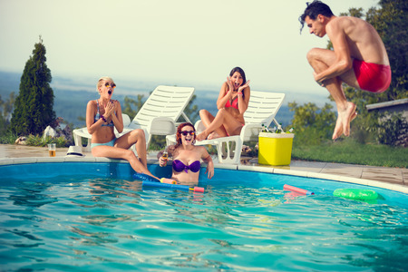 Photo for Young in pool scared look his male friend while jumps in open pool - Royalty Free Image