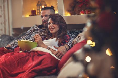 Foto de Young man and woman in bed watching tv and eating pop corn - Imagen libre de derechos