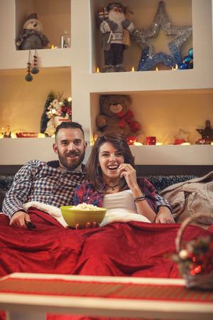 Foto de Young pair in bed in hug eating popcorn while watching movie on tv - Imagen libre de derechos