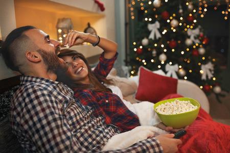 Foto de Couple in love at Christmas eve enjoy with popcorn while watching tv - Imagen libre de derechos