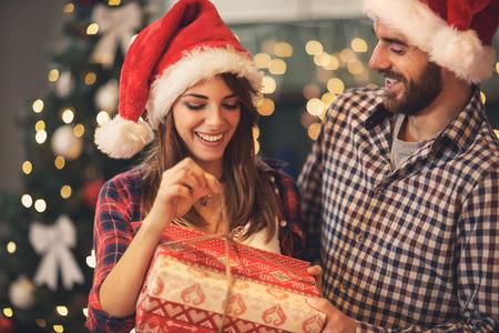 Foto de Cheerful man and woman opens Christmas gift - Imagen libre de derechos