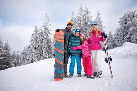 Foto de Happy family enjoying in winter vacations together in mountains - Imagen libre de derechos