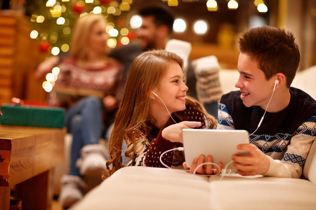 Photo for Cheerful girl and boy listening music on tablet together - Royalty Free Image