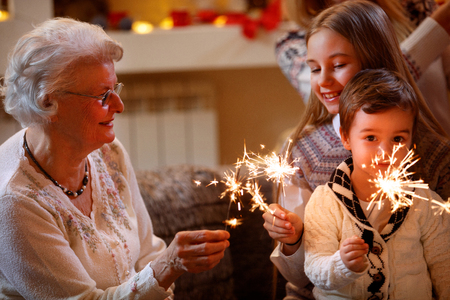 Foto de smiling grandchildren and grandparents with sprinklers celebrating xmas  - Imagen libre de derechos