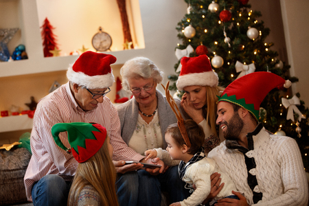 Photo for Children with grandparents looking  Christmas photos on cell phone  - Royalty Free Image