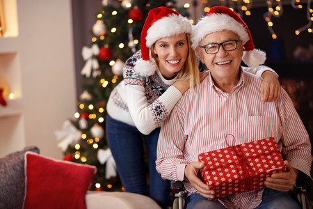 Photo pour smiling daughter and elderly father in wheelchair celebrating Christmas together  - image libre de droit