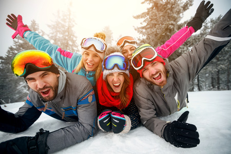 Foto de Group of friends on winter holidays – Happy skiers lying on snow and having fun  - Imagen libre de derechos