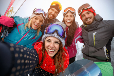 Photo pour Group of smiling friends having fun on the snow and making selfie - image libre de droit