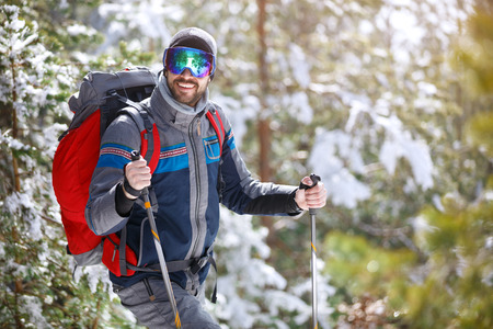 Photo pour Smiling hiker with equipment hiking thru forest - image libre de droit
