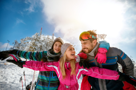 Foto de Happy family laughing and enjoying in winter vacations together on the mountain - Imagen libre de derechos