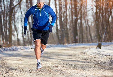 Photo pour Male sprinter running in nature in the winter   - image libre de droit