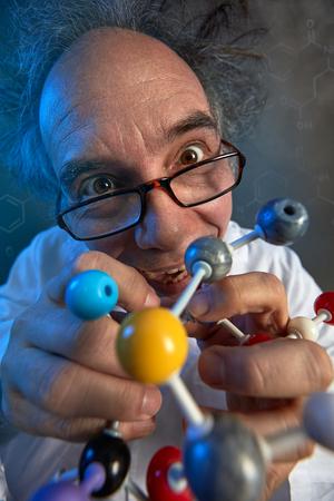 Foto de Crazy scientist with model molecules building a new chemical compound - Imagen libre de derechos
