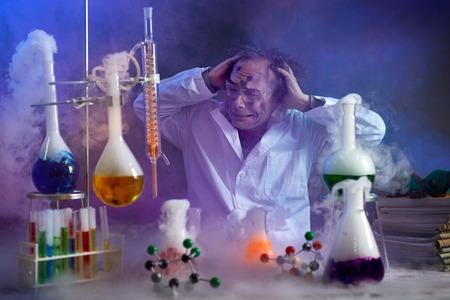 Foto de Disappointed chemist looking in his failed experiment in smoke of explosion - Imagen libre de derechos