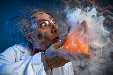 Foto de  Crazy chemist with dirty face holding  test-tube - Imagen libre de derechos