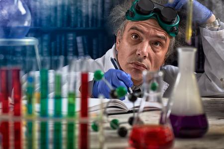 Foto de Thinking chemist  near equipment observing experiment in lab  - Imagen libre de derechos