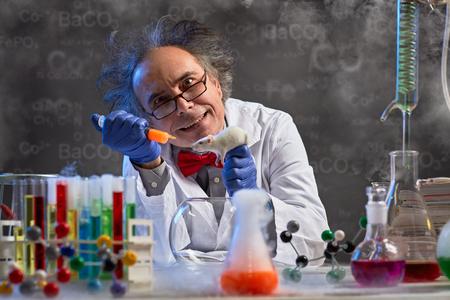 Foto de  crazy chemistry professor injecting lab mouse for his wacky experiment - Imagen libre de derechos