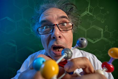 Foto de  Funny scientist adjusts model molecules for his new scientific discoveries - Imagen libre de derechos