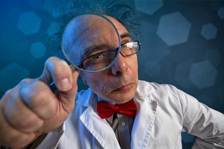 Foto de scientist in a white coat doing analyze looking through a magnifying glass - Imagen libre de derechos
