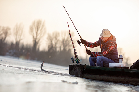 Foto de ice fishing on frozen lake- senior fisherman catch fish - Imagen libre de derechos