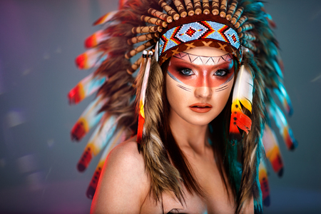 Photo pour Portrait of young girl in costume native American Indian background - image libre de droit