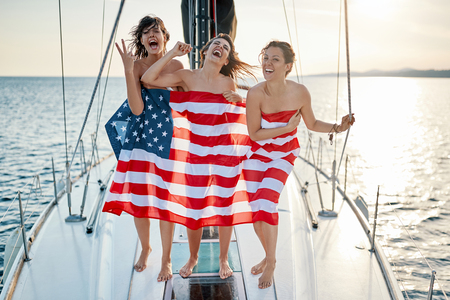 Foto per Sexy happy young girls on the yacht in American flag - Immagine Royalty Free