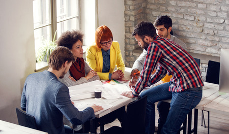 Photo for Team of designers reviewing plans and working together in office - Royalty Free Image