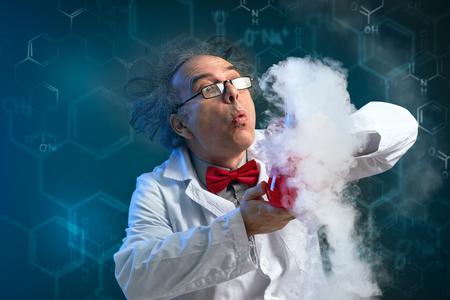 Foto de Crazy chemist holding his success experiment with test-tube and lot of smoke - Imagen libre de derechos