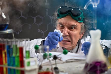 Foto de Angry chemist  wreak their displeasure on crumpled paper - Imagen libre de derechos