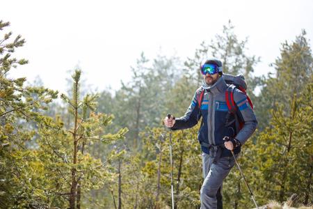Photo pour Smiling male hiker hiking in forest - image libre de droit