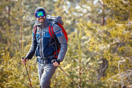 Photo pour Smiling male hiking in snowy forest - image libre de droit