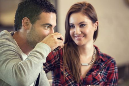 Foto per Amorous girl looking her boyfriend while drink coffee - Immagine Royalty Free