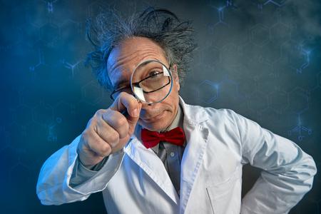 Foto de Funny scientist in white coat looking through a magnifying glass - Imagen libre de derechos