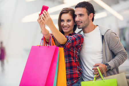 Photo for Happy couple taking a photo in the shopping mall - Royalty Free Image