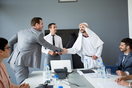 Photo for Arabian partner handshake with businessman at office - Royalty Free Image