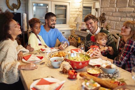 Photo pour Smiling multi ethnic friends have fun at a family Christmas dinner - image libre de droit