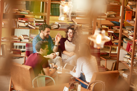 Photo pour Two young men and women in conversation in library - image libre de droit