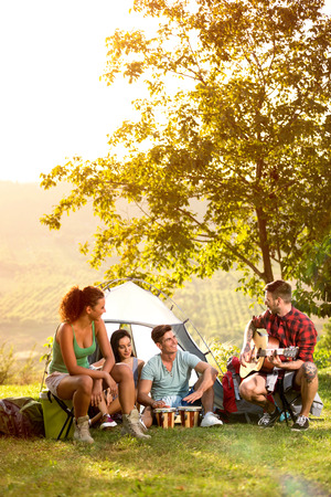 Photo pour young people on camping trip to play and sing, relaxing on vacation - image libre de droit