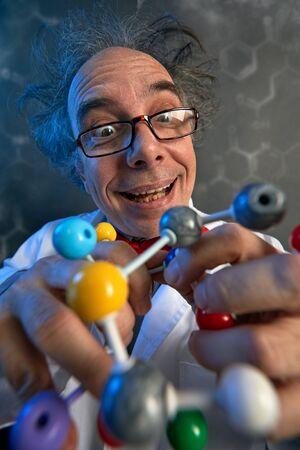 Foto de Funny scientist holding structure of model molecules with atoms in different colors - Imagen libre de derechos
