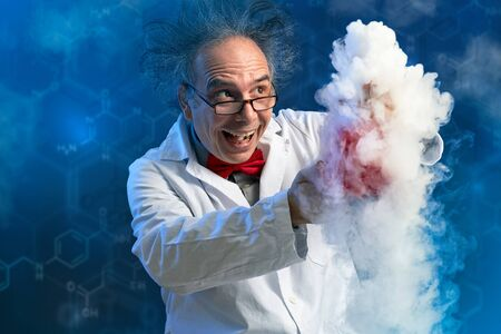 Foto de Happy crazy chemist with his experiment from which spews smoke - Imagen libre de derechos