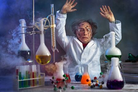 Foto de Crazy scientist with dirty face in lab surrounded by the smoke from the explosion - Imagen libre de derechos