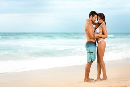 Photo pour young couple in love embracing  on beach - image libre de droit