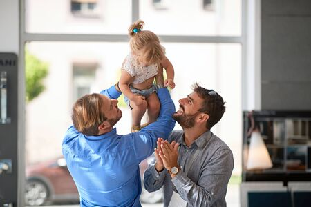 Photo pour Smiling gay couple with child girl - image libre de droit