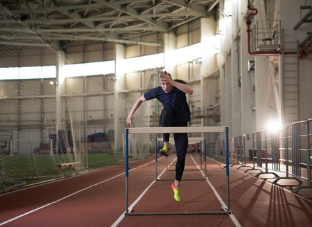 Photo for The shot of concentrated male track and field athlete jumping over the hurdle - Royalty Free Image