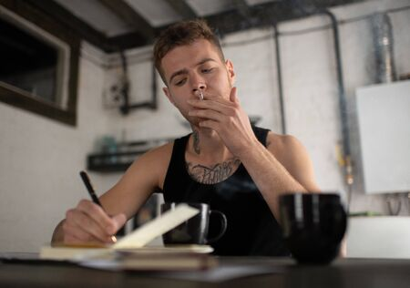 Photo for Concentrated hipster songwriter smoking cigarette while working at home - Royalty Free Image
