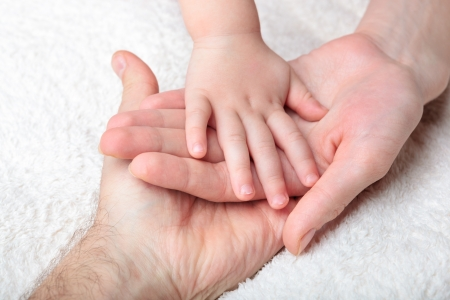 Photo for Closeup of baby hand into mother and father hands - Royalty Free Image